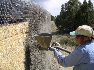 Spraying stucco on a fence